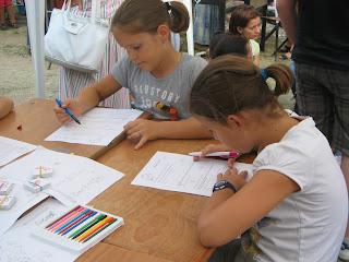 Két copfos lányka szövegértéses feladatlapokat old az összetolt asztalok sarkánál. Kezükben írószer, a feladatlapra hajolnak. Maximális a koncentrálás.