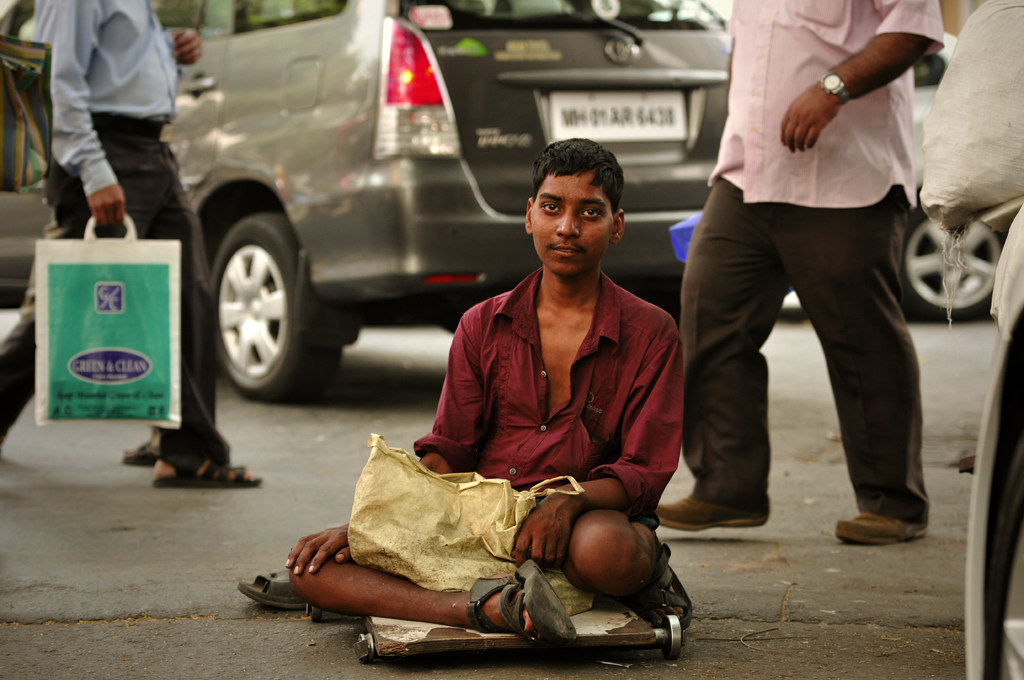 This is a photo of a young man in Mumbai on a board on wheels