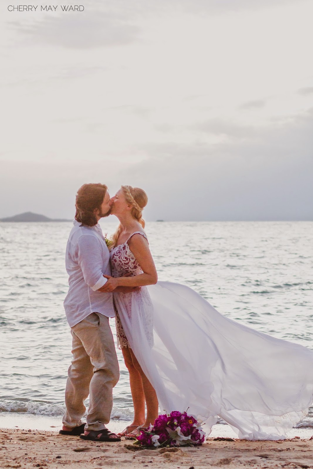 bride and groom kissing on the beach, destination wedding on Koh Samui Thailand, beautiful wedding photos, wedding dress blowing in the wind,
