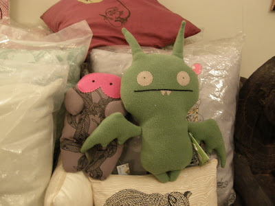 A green Ugly Doll with bat wings and other merchandise at The Alternative Cafe, including an owl pillow