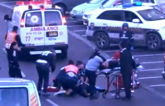 First responders give first-aid after two Palestinian men attacked a synagogue in Jerusalem  (Screen capture from YouTube video)