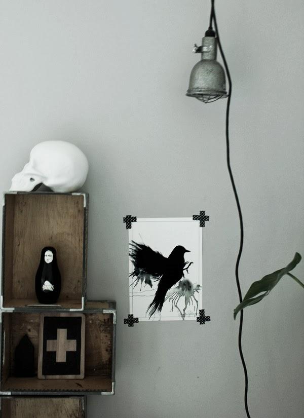 poster i svart och vitt, svart fågel, illustrationer, tavlor, inspiration tavlor, artprints, babuschka, rysk docka, svarta detaljer, inredning, hängande bygglampa, kors, dödskalle av porslin, trälådor mot vägg,