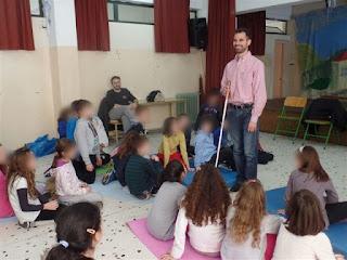 Ο Βαγγέλης Αυγουλάς με το λευκό μπαστούνι ανάμεσα στα παιδιά τους δείχνει πως το χρησιμοποιεί!
