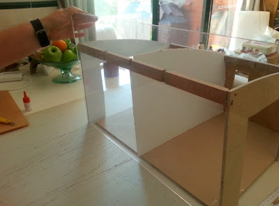 A piece of perspex held up in front of a dry-fitted dolls' house kit.