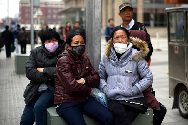 A group of Chinese women wear face masks as they sit on a street side in Beijing on April 19, 2013.