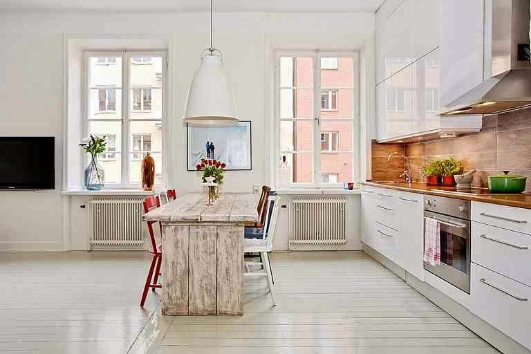 Skandynawska aranżacja, biała kuchnia i czerwone krzesła