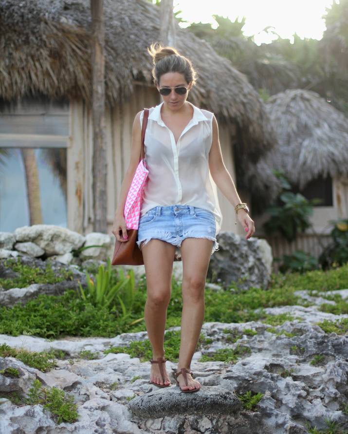 Fashion blogger Mónica Sors from Mes Voyages à Paris blog wearing transparent blouse, denim shorts and sandals, in Tulum, Cancun.