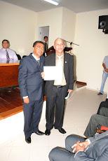 Prof. Adailton  recebendo o Título  das mãos do vereador helinho, autor do projeto.