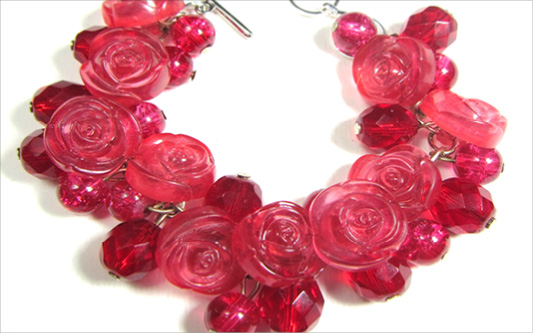Pretty bracelet has red flower buttons and clusters of shiny Czech beads