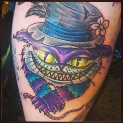 Gato sorridente usando chapéu tatuagem
