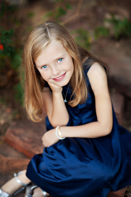 Beautiful blond child sitting on rocks in a Tucson backyard