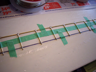Soldering the brass rods together to form the chain link fence's frame