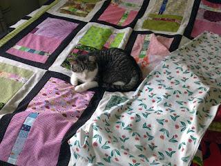 Tilkkupinta sängyllä silitettynä, kissa tilkkupinnalla