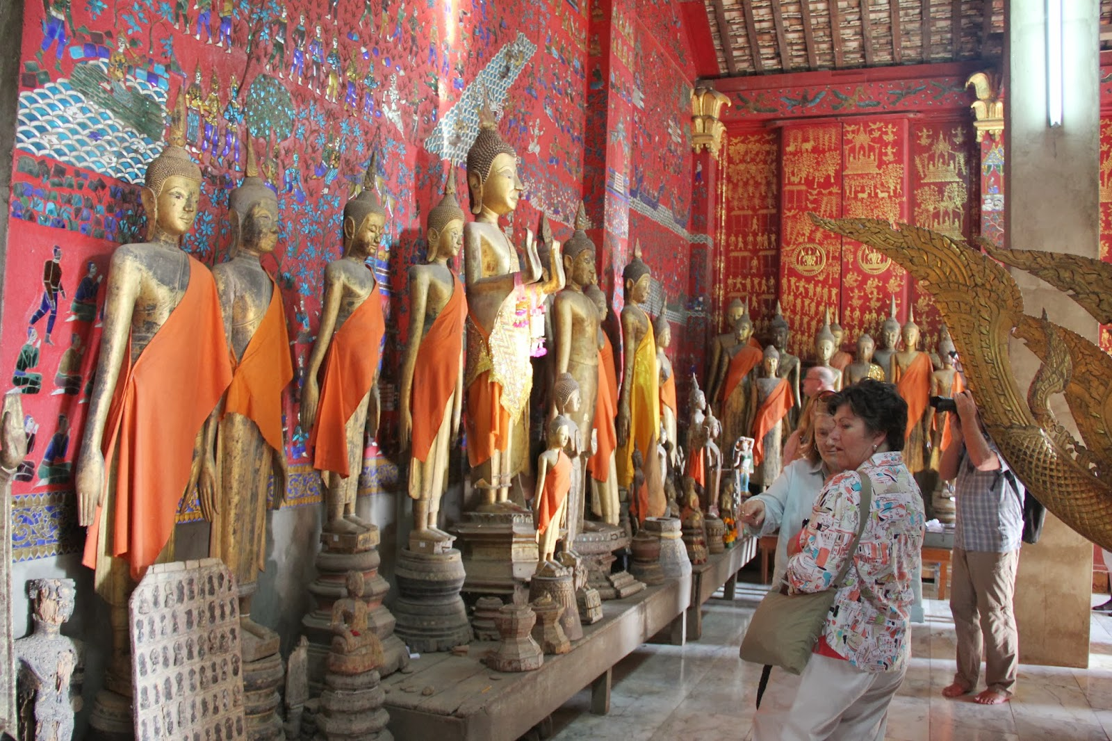 Saffron-robed Buddha statues at Wat Xien Thong.
