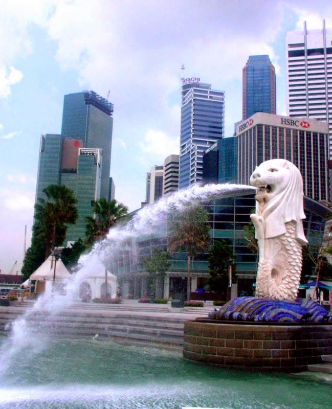 """Merlion adalah sebuah patung dengan kepala singa dan berbadan ikan yang sudah menjadi maskot Singapura. Nama Merlion merupakan gabungan dari """"mermaid"""" dan """"lion"""" atau dalam bahasa Indonesia adalah ikan duyung dan singa. Taman Merlion Park buka 24 jam setiap hari dan tidak dipungut biaya bagi siapapun yang ingin berkunjung, sehingga anda dapat menghemat biaya perjalanan anda. Selain berfoto-foto anda juga dapat menikmati sungai di lokasi ini karena Merlion Park terletak di depan Singapore River."""