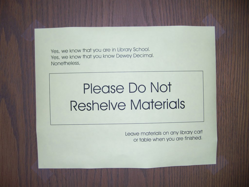 Sign taped to wood paneling reads in small letters, upper left: 'Yes, we know that you are in Library School. Yes, we know that you know Dewey Decimal. Nonetheless.' In large letters, centered horizontally and vertically: 'Please Do Not Reshelve Materials.' In small letters, lower right: 'Leave materials on any library cart or table when you are finished.'
