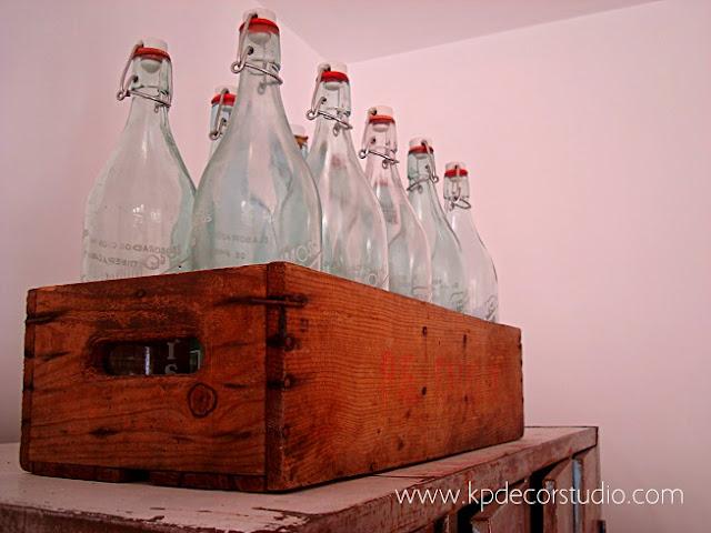 Decorar con botellas de cristal vintage y cajas de envases de madera antiguas. Decoradores en Valencia y Madrid