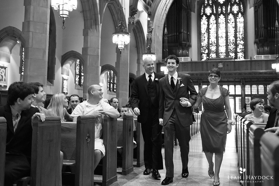 Groom walking down church aisle with both parents