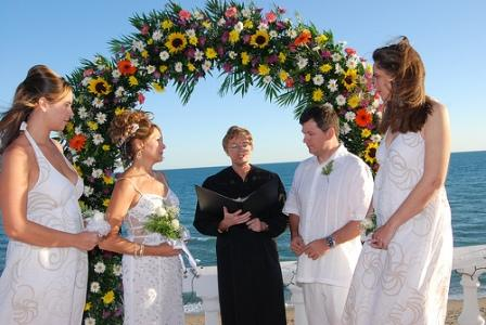 Bridal arch situated on the beach decorated with bright flowers and greenery