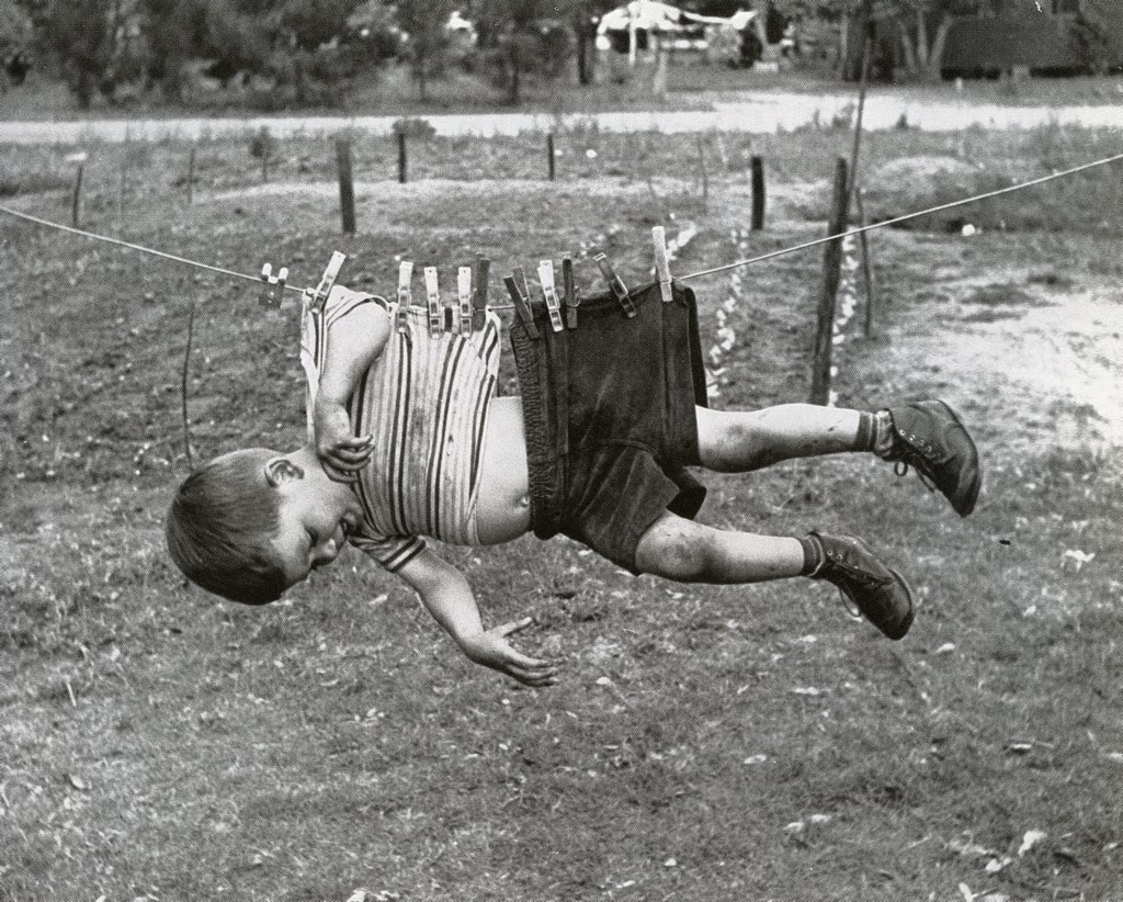 A picture of a boy hanging from a clothesline by a series of clothespins attached to his shirt and pants.