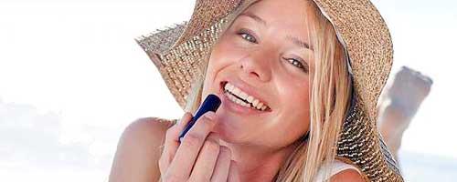 chica pintandose los labios en la playa