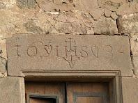 Detall de la llinda d'una de les finestres amb la inscripció de l'any 1634 i entre les seves xifres l'acrònim de Jesús