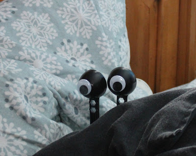 googly eyes hiding in bed