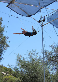 Noah looking for the catch bar in a knee hang on the flying trapeze.