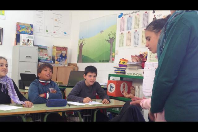 en la imagen se ve a los actores secundario hablando en clase con la protagonista