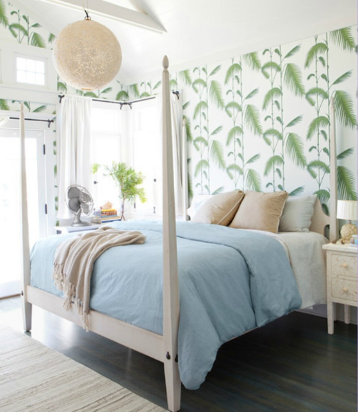 Coastal bedroom with white four poster bed and palm frond wallpaper