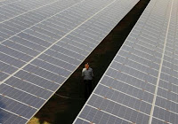 A private security guard walks between rows of photovoltaic solar panels inside a solar power plant at Raisan village near Gandhinagar, in the western Indian state of Gujarat, February 11, 2014. (Credit: Reuters/Amit Dave) Click to Enlarge.