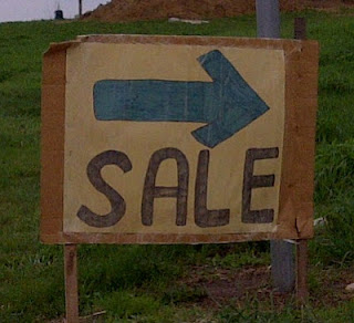 "Cardboard sign with ""Sale"" in large black letters and green directional arrow"