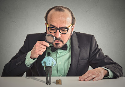 A professor type is looking through a magnifying glass at a miniature job candidate