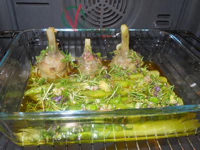 Bandeja con los espárragos y alcachofas en el horno.