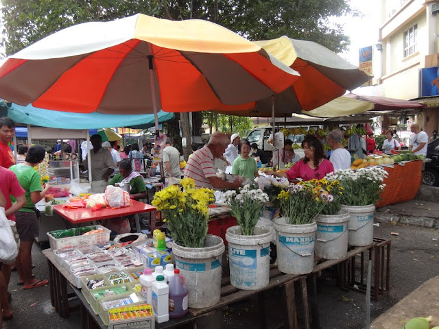 Vendors sell flowers and fruits in the morning market in Malaysia