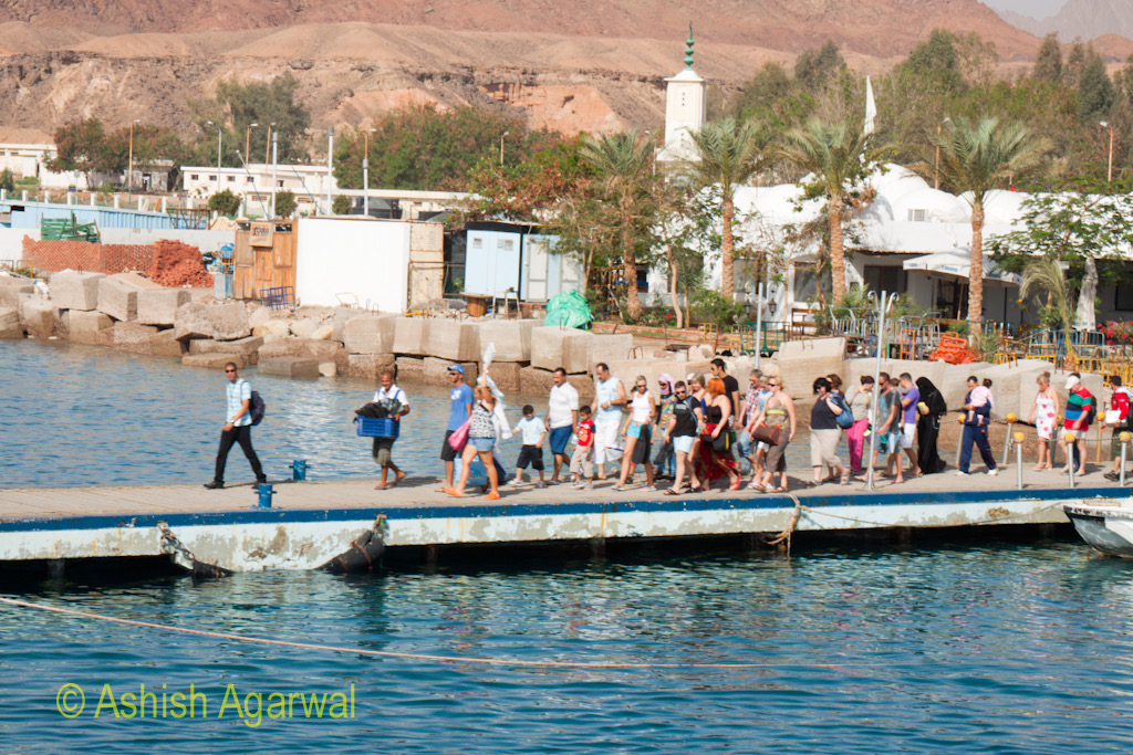 Tourists walking on the pier that leads to a yacht at the Red Sea in Sharm el Sheikh