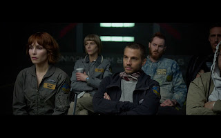 Prometheus crew sitting down inside spaceship wearing uniforms
