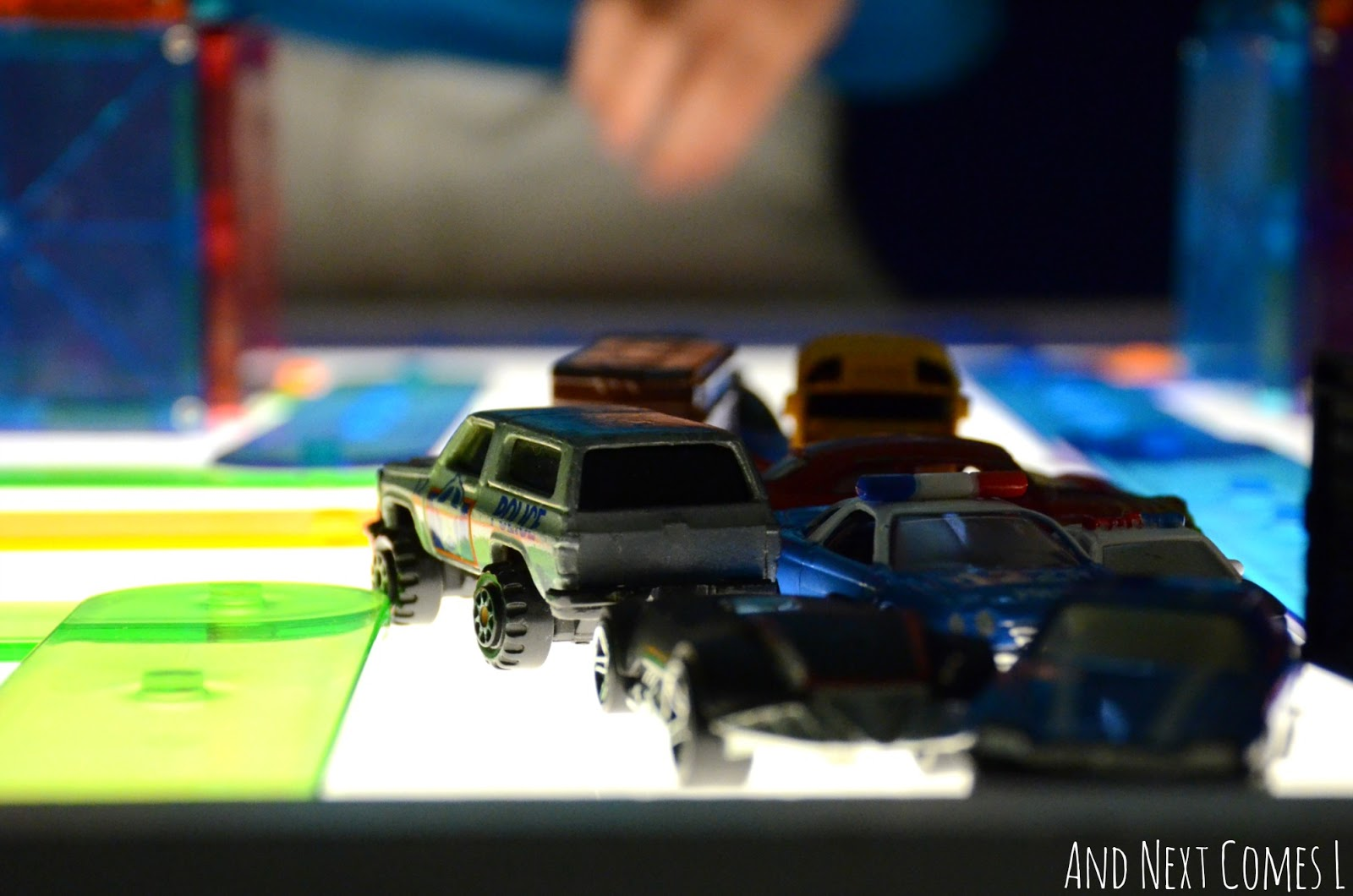 Playing with cars on the light table from And Next Comes L