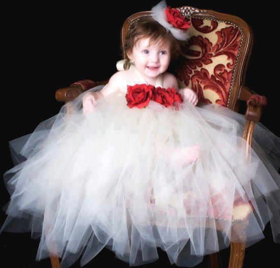 The whole white frock is complementing the skin tone of a baby. On chest one side there is a bunch of three flowers attached and from waist, it is made wide enough. Even .