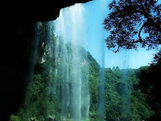 Cascata Salto Ventoso visto da Caverna Salto Ventoso, em Farroupilha. Queda d'água emoldurada pelas paredes da caverna e mata nativa ao fundo.