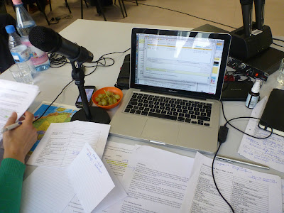 Blick auf den Dolmetschertisch (ohne Kabine drumherum): Notizen, Manuskripte, Laptop, Landkarte, Mikro, Stimmöl
