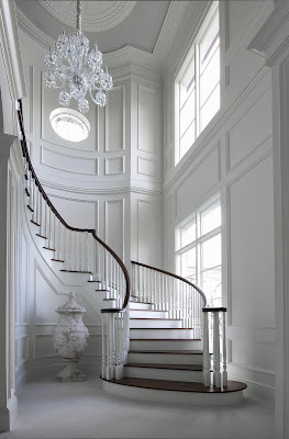 a wonderful white and wooden finish stairs with luxury chandelier hovering above