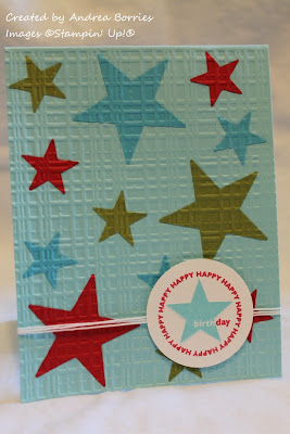 Light blue card with small and large green, turquoise and red stars, all with a plaid embossed texture.