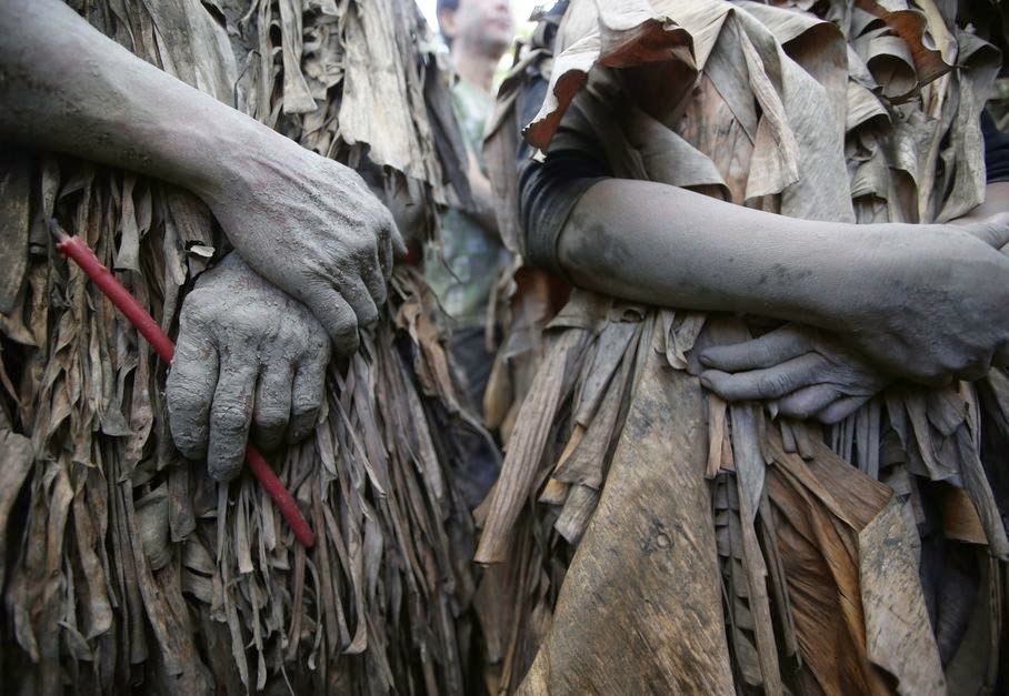 Residents, who are covered in mud and wrapped in dried Banana leaves, attend a mass to celebrate the Feast Day of St. John the Baptist at the village of Bibiclat, Aliaga township, Nueva Ecija province in northern Philippines, Tuesday, June 24, 2014. The unique annual tradition dates back to the 1940's.