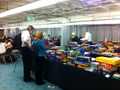 Three tables with hundreds of board games on them