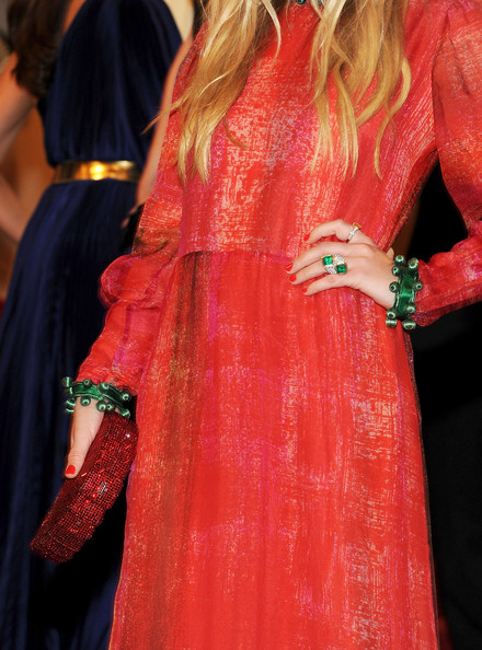 Mary-Kate Olsen wearing a Van Cleef & Arpels emerald ring and pair of green baubles bracelets and neck-piece and a Judith Leiber red sequined Flip Top clutch at the 2011 MET gala.