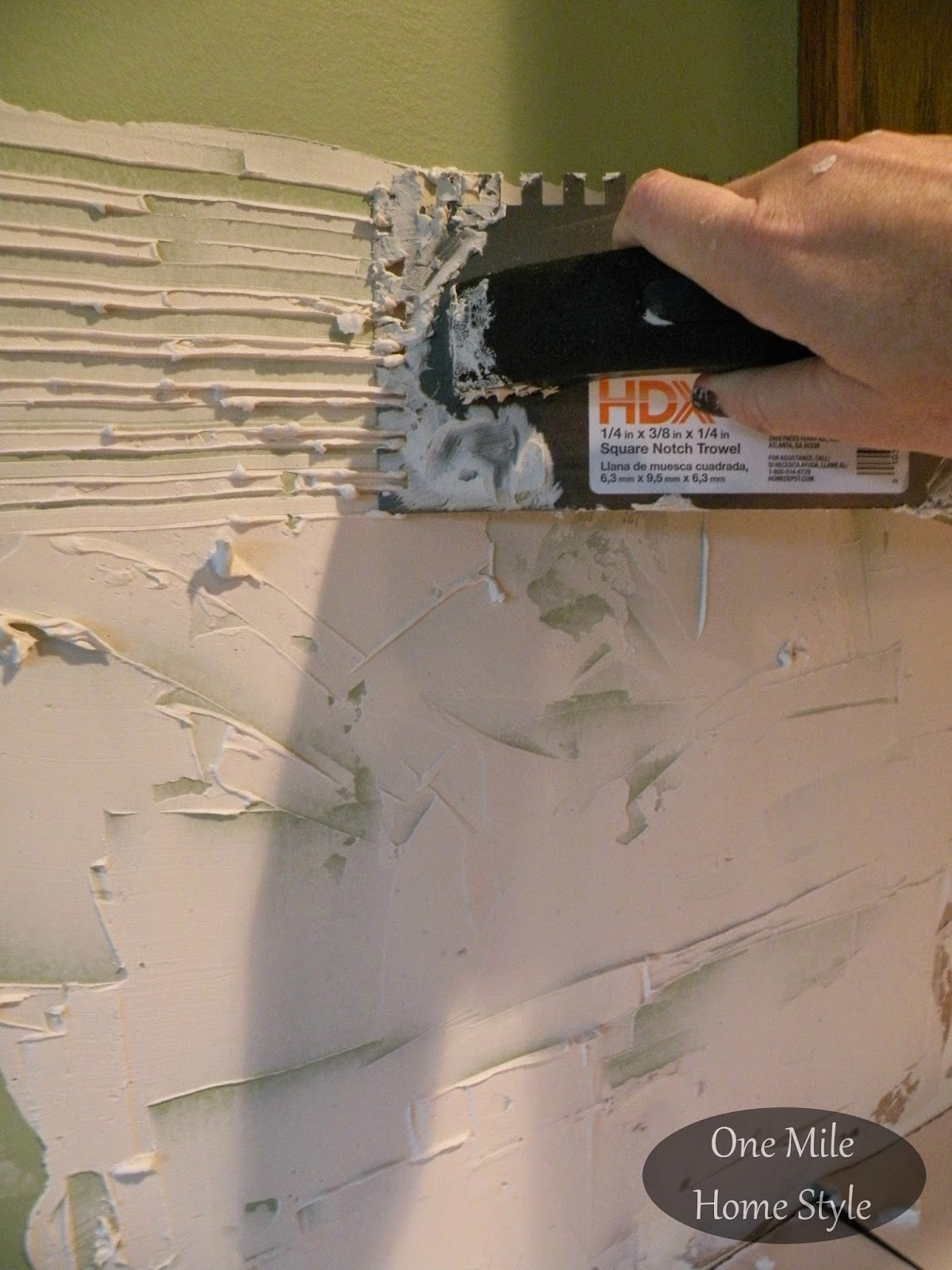 Applying tile adhesive to the walls for a new backsplash