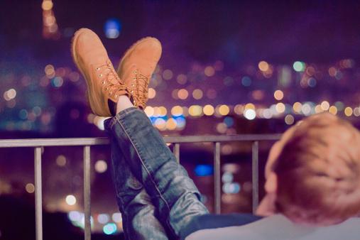 Homem sentado em uma cadeira relaxando olhando para a cidade