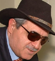 A photo of the painter Esref Armagan. He is wearing sunglasses, a navy blue suit, a red necktie, and a wide-brimmed brown dress hat. Looking good! Credit: Esref Armagan