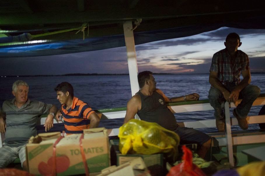 "In this May 22, 2014, photo, men chat as they travel in the ""Almirante Barbosa"" regional boat, on the Solimoes river near Manaus, Brazil. The lumbering wooden vessels are slow going _ the ""Almirante Barbosa"" chugs at some 20 kilometers (12 miles) an hour, with trips that can stretch out for days or even weeks."